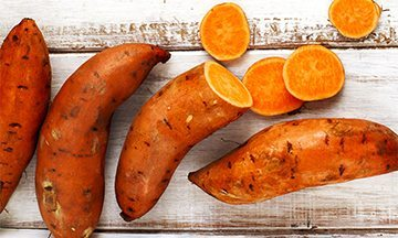 Raw sweet potatoes on wooden background